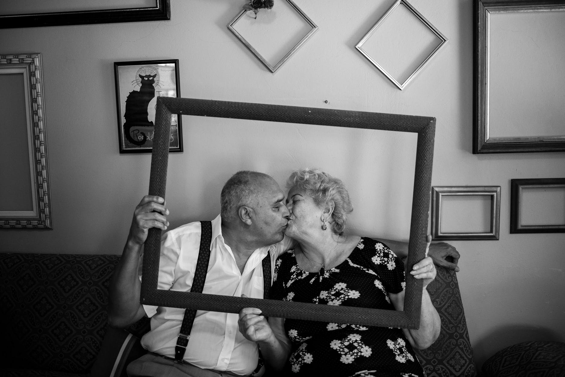 grayscale photo of couple holding frame while kissing