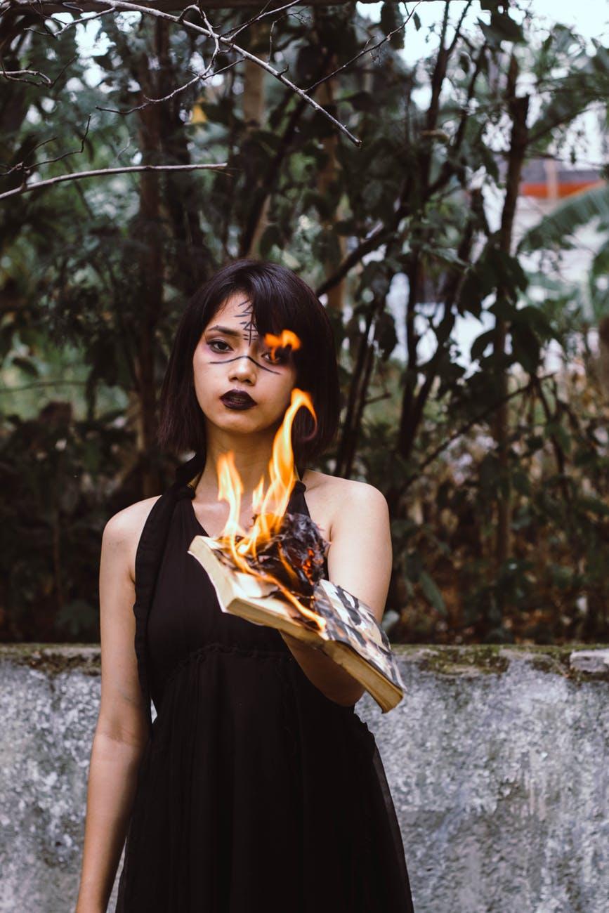 woman wearing black sleeveless dress while holding burned book